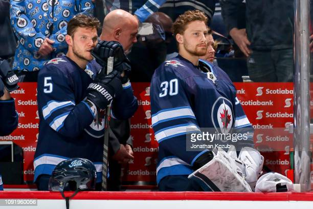 Dmitry Kulikov and goaltender Laurent Brossoit of the Winnipeg Jets look on from the bench during the singing of the National anthems prior to puck...