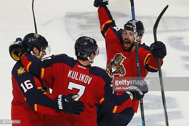 Dmitry Kulikov is congratulated by Aleksander Barkov and Erik Gudbranson of the Florida Panthers after scoring an empty net goal against the New York...