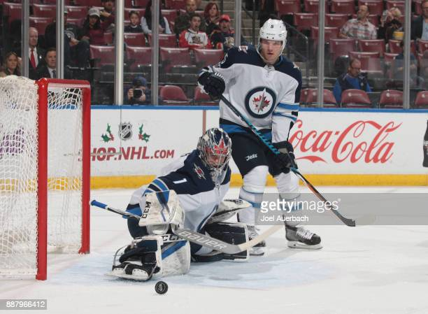 Dmitry Kulikov looks down as goaltender Eric Comrie of the Winnipeg Jets stops a shot by the Florida Panthers during first period action at the BBT...