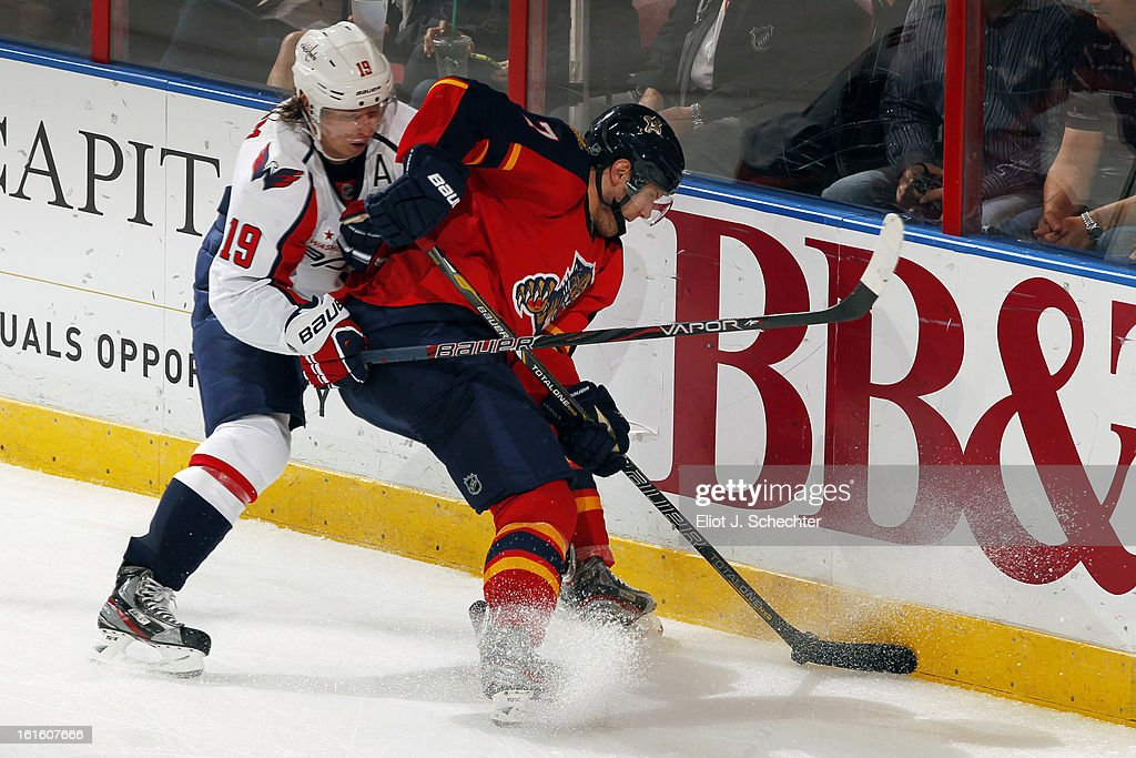 Dmitry Kulikov #7 of the Florida Panthers digs the puck out from the boards against Nicklas Backstrom #19 of the Washington Capitals at the BB&T Center on February 12, 2013 in Sunrise, Florida.