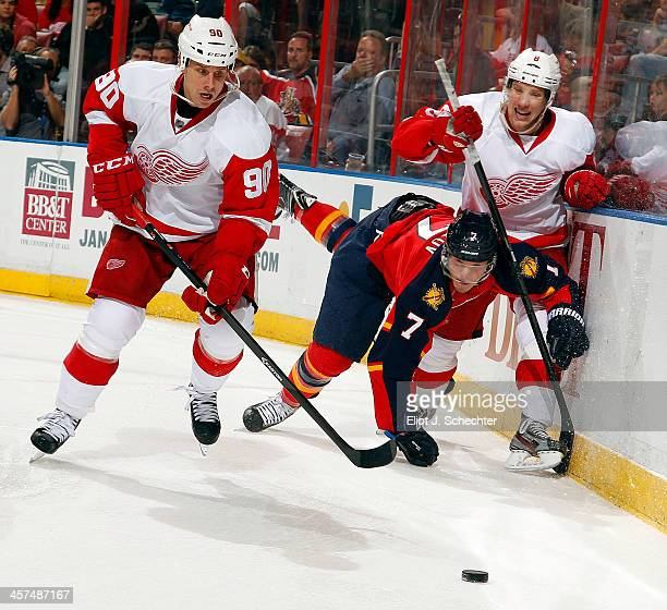 Dmitry Kulikov of the Florida Panthers tangles with Stephen Weiss and Justin Abdelkader of the Detroit Red Wings at the BBT Center on December 10...