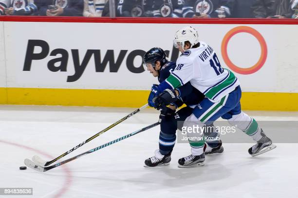 Dmitry Kulikov of the Winnipeg Jets and Jake Virtanen of the Vancouver Canucks battle for the loose puck during second period action at the Bell MTS...