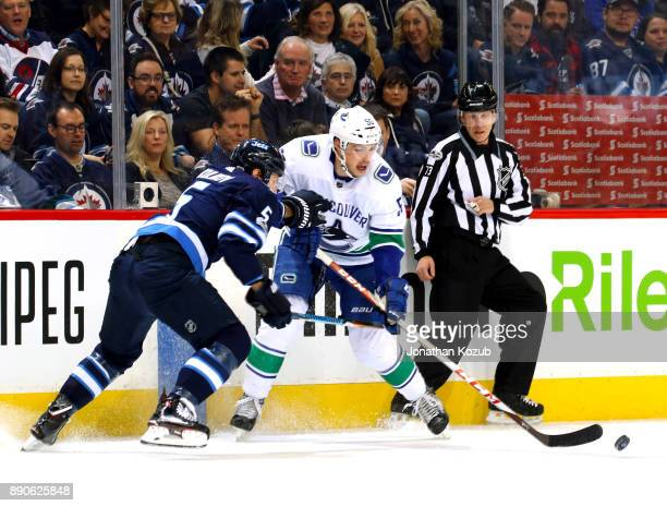 Dmitry Kulikov of the Winnipeg Jets battles Brendan Gaunce of the Vancouver Canucks for the loose puck during first period action at the Bell MTS...