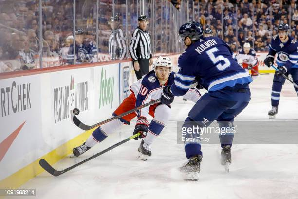 Dmitry Kulikov of the Winnipeg Jets chips the puck past a defending Alexander Wennberg of the Columbus Blue Jackets during third period action at the...