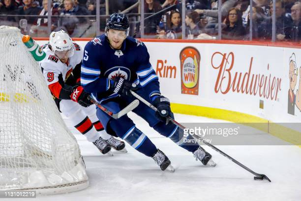 Dmitry Kulikov of the Winnipeg Jets plays the puck behind the net as Bobby Ryan of the Ottawa Senators gives chase during third period action at the...