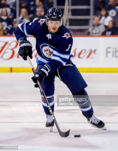 Dmitry Kulikov of the Winnipeg Jets plays the puck down the ice during first period action against the Ottawa Senators at the Bell MTS Place on...
