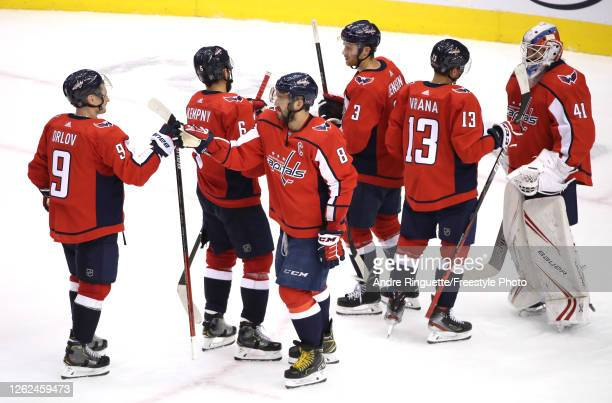 Dmitry Orlov and Alex Ovechkin of the Washington Capitals celebrate the win over the Carolina Hurricanes with teammates Michal Kempny, Nick Jensen,...
