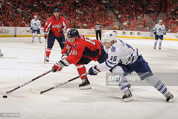 Dmitry Orlov of the Washington Capitals and Matthew Lombardi of the Toronto Maple Leafs fight for the puck during a NHL hockey game on March 11 2012...