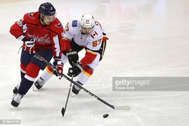 Dmitry Orlov of the Washington Capitals and Michael Frolik of the Calgary Flames battle for the puck during the first period at Capital One Arena on...
