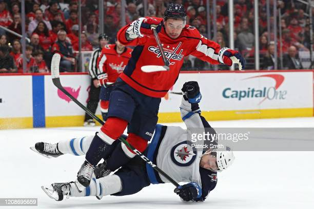 Dmitry Orlov of the Washington Capitals checks Neal Pionk of the Winnipeg Jets during the second period at Capital One Arena on February 25 2020 in...