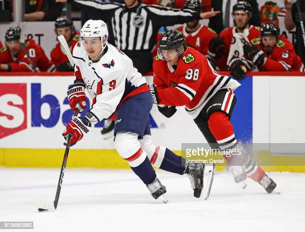 Dmitry Orlov of the Washington Capitals is chased by Patrick Kane of the Chicago Blackhawks at the United Center on February 17 2018 in Chicago...