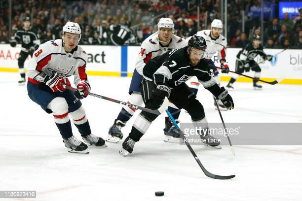 Dmitry Orlov of the Washington Capitals John Carlson of the Washington Capitals and Oscar Fantenberg of the Los Angeles Kings fight for control of...