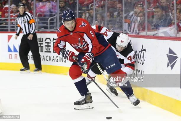 Dmitry Orlov of the Washington Capitals skates with the puck as Miles Wood of the New Jersey Devils chases at Capital One Arena on December 30 2017...