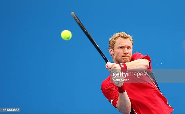 Dmitry Tursunov of Russia plays a backhand in his match against Lukas Rosol of the Czech Republic during day four of the 2014 Sydney International at...