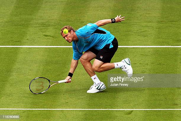 Dmitry Tursunov of Russia returns a shot during his Men's Singles first round match against Feliciano Lopez of Spain on day one of the AEGON...