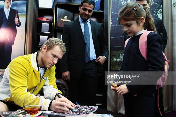 Dmitry Tursunov of Russia signs his autograph for a young fan during day five of the International Tennis Tournament St Petersburg Open 2010 at the...