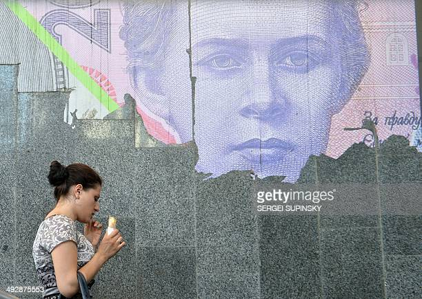 Dmitry ZAKS A woman eats icecream next to a torned poster depicting Ukrainian 200hrivnya banknote at the metro entrance in Kiev on May 22 2014The...