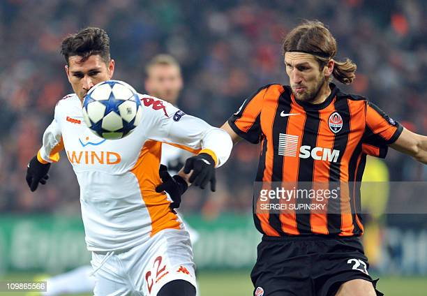 Dmytro Chygrynskiy of FC Shakhtar vies for a ball with Marco Borriello of AS Roma during UEFA Champions League football match in Donetsk on March 8...