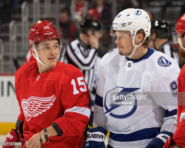 Dmytro Timashov of the Detroit Red Wings looks back at Mikhail Sergachev of the Tampa Bay Lightning during an NHL game at Little Caesars Arena on...