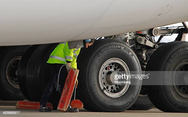 A Dnata ground crew member places wheel chocks around the Michelin Air X tires of an Airbus A380 aircraft operated by Emirates at Terminal 3 of...