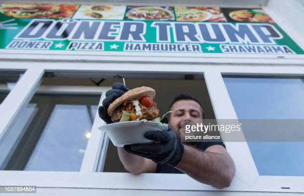 Döner seller Hadi Daoud holding a Döner sandwich out of the window of the 'Döner Trump' shop in Bielefeld Germany 20 January 2017 At the Bielefeld...