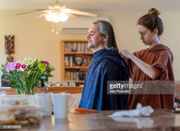 do it yourself - home haircut. late teenage girl, a daughter, gives a haircut to her father, mature 50-years-old man with long hair. - alex potemkin coronavirus stock pictures, royalty-free photos & images