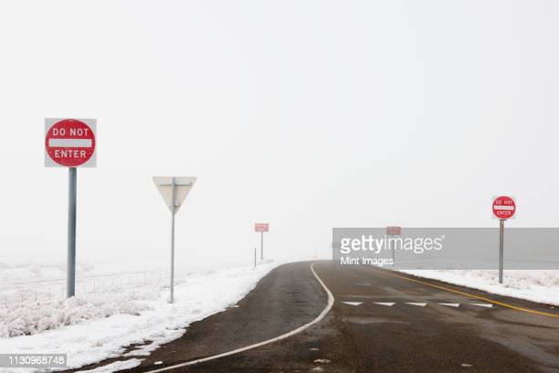 'do not enter' signs by snowy road - wrong way stock pictures, royalty-free photos & images
