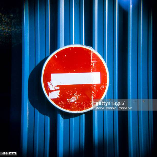 'Do not enter' traffic sign on a blue metal fence