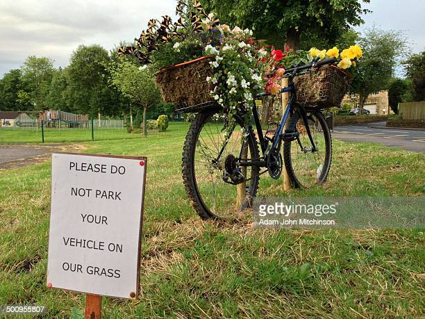 Do not park sign ignored by flower decorated bike along Tour de France route through Pool in Wharfedale West Yorkshire UK