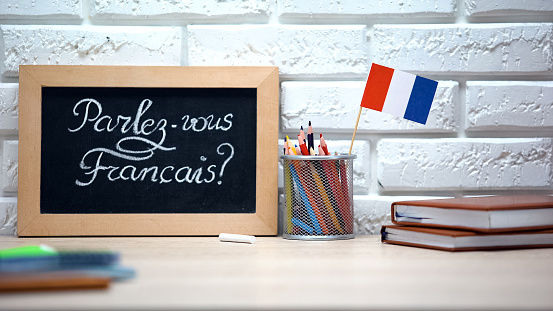 Do you speak French written on board, France flag standing in box, language 1169984447
