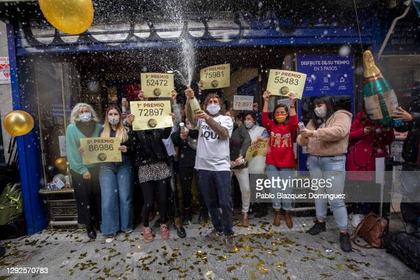 Doña Manolita' lottery shop owners and employees celebrate after selling the winning ticket number of Spain's Christmas lottery named 'El Gordo'...