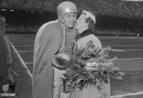 Doak Walker of the Detroit Lions is kissed by wife Norma during a ceremony at half time honoring the record breaking player at Briggs Stadium as the...