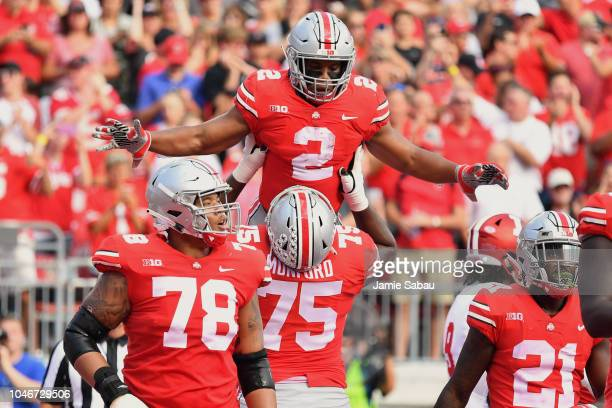 K Dobbins of the Ohio State Buckeyes celebrates his first quarter touchdown run against the Indiana Hoosiers with Thayer Munford of the Ohio State...