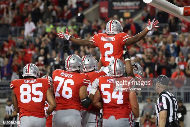 K Dobbins of the Ohio State Buckeyes celebrates with teammates after scoring a 6yard rushing touchdown during the third quarter against the Oklahoma...