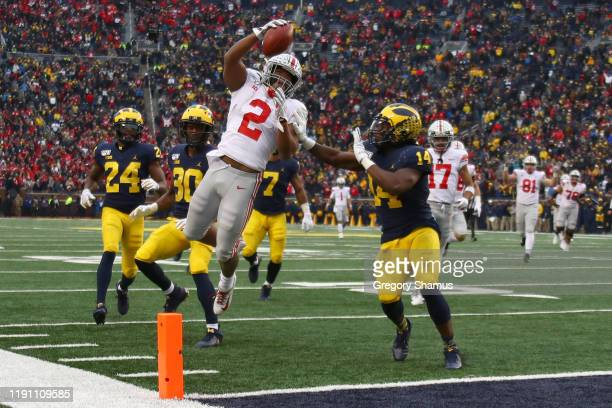 K Dobbins of the Ohio State Buckeyes dives for a fourth quarter touchdown past Josh Metellus of the Michigan Wolverines at Michigan Stadium on...