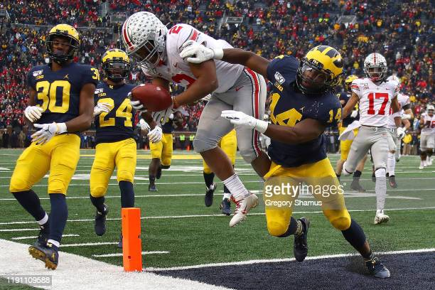 Dobbins of the Ohio State Buckeyes dives for a fourth quarter touchdown past Josh Metellus of the Michigan Wolverines at Michigan Stadium on November...