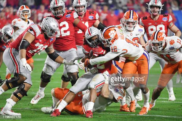 Dobbins of the Ohio State Buckeyes is tackled by K'Von Wallace of the Clemson Tigers in the first half during the College Football Playoff Semifinal...