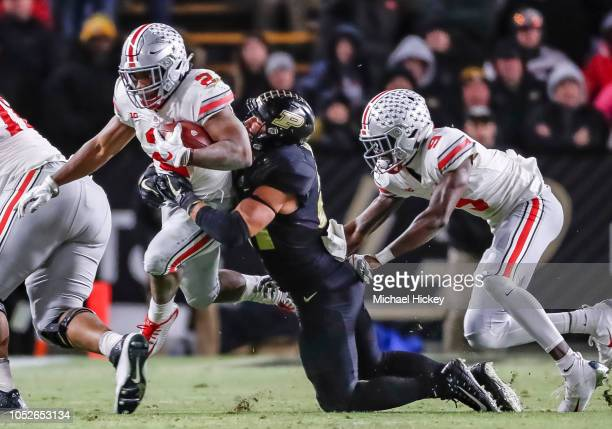 Dobbins of the Ohio State Buckeyes runs the ball as Markus Bailey of the Purdue Boilermakers hangs on for the stop at Ross-Ade Stadium on October 20,...