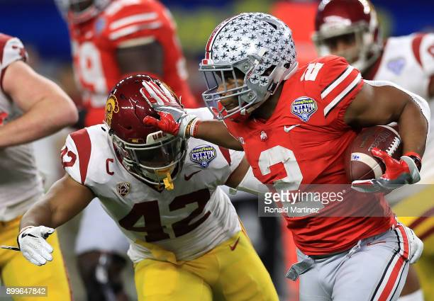 K Dobbins of the Ohio State Buckeyes runs the ball past Uchenna Nwosu of the USC Trojans in the second quarter during the Goodyear Cotton Bowl at ATT...
