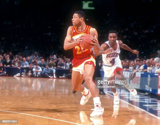 Doc Rivers of the Atlanta Hawks looks to pass as Andre Turner of the Philadelphia 76ers defends during an NBA game on February 27 1991 at the...