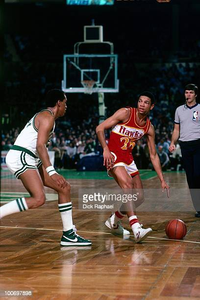 Doc Rivers of the Atlanta Hawks moves the ball up court against Dennis Johnson of the Boston Celtics during a game played in 1984 at the Boston...