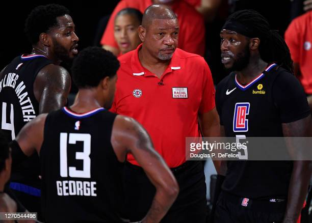 Doc Rivers of the LA Clippers talks with Montrezl Harrell of the LA Clippers and Paul George of the LA Clippers during the fourth quarter against the...