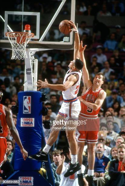 Doc Rivers of the New York Knicks goes up for a slam dunk over John Paxson of the Chicago Bulls during an NBA basketball game circa 1993 at Madison...