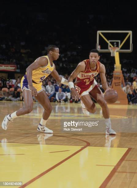 Doc Rivers, Point Guard for the Atlanta Hawks dribbles the basketball past Byron Scott of the Los Angeles Lakers during their NBA Pacific Division...