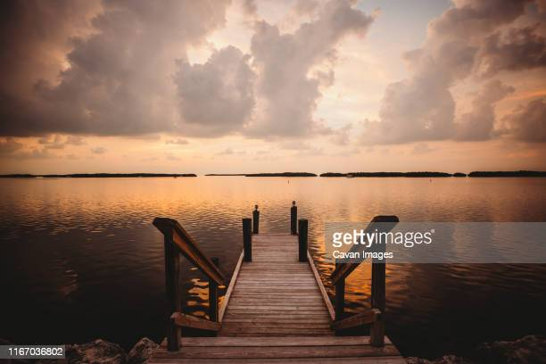 a dock at sunset in the florida keys is the perfect spot for relaxing - florida keys stock pictures, royalty-free photos & images