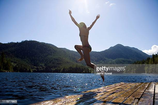 dock jumping into lake on sunny day with blue sky - kelowna stock pictures, royalty-free photos & images