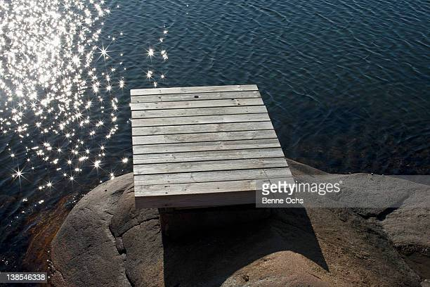 dock on boulder by water's edge - rivage photos et images de collection