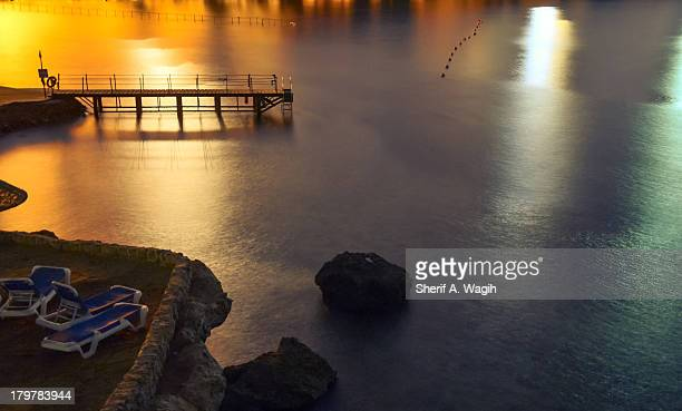 Dock on the ocean with lights and beach chairs