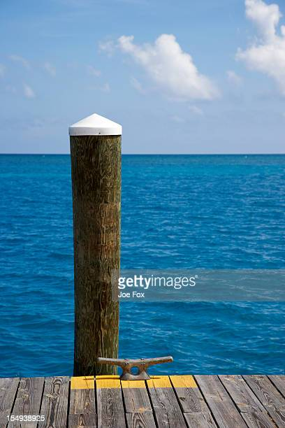 Dock piling, boat cleat and empty sea