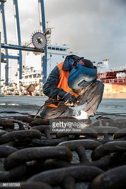 Dock welder welding chain on waterfront